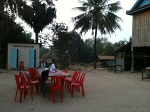 Homestay loo (blue door) on the left, dining table in the middle, house on the right