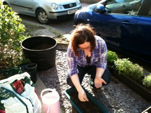 8. Plant something: me planting seeds outside my flat in the UK